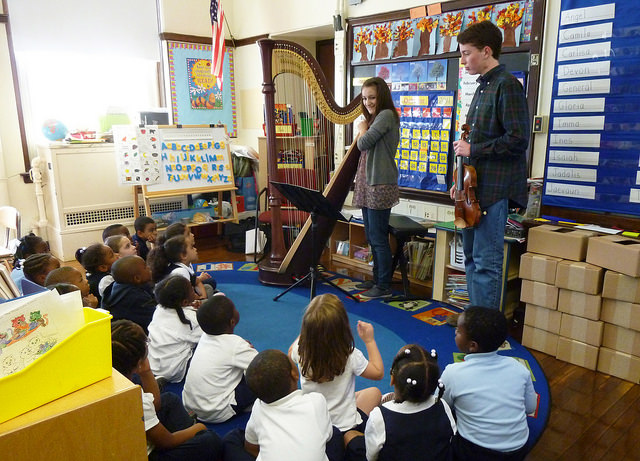 A young white female harpist, with long brown hair, stands next to a full sized harp, and a young white male violinist, in front of a school room full of elementary students