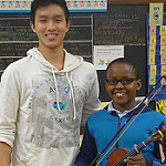 A teenager boy in a white hoodie stands next to an elementary school violin player.