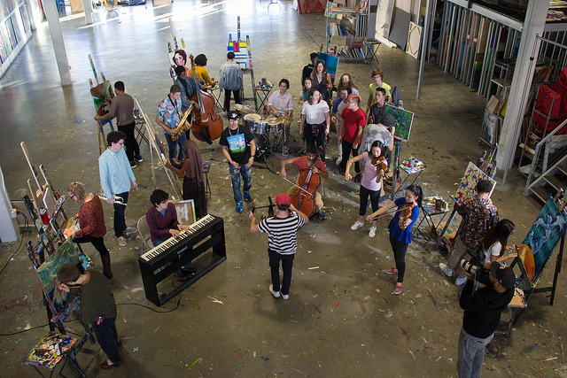 From overhead, the camera looks down on 26 young musicians and artists in brightly colored clothes, arrayed across a paint splattered floor. There are two cameramen filming.