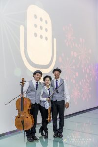 Noah Lee, with his cello, poses next to his fellow musicians in front of a From the Top logo projected on a white wall.