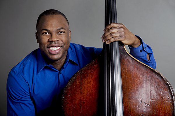 Joseph Conyers smiles at the camera while holding his double bass at his side.