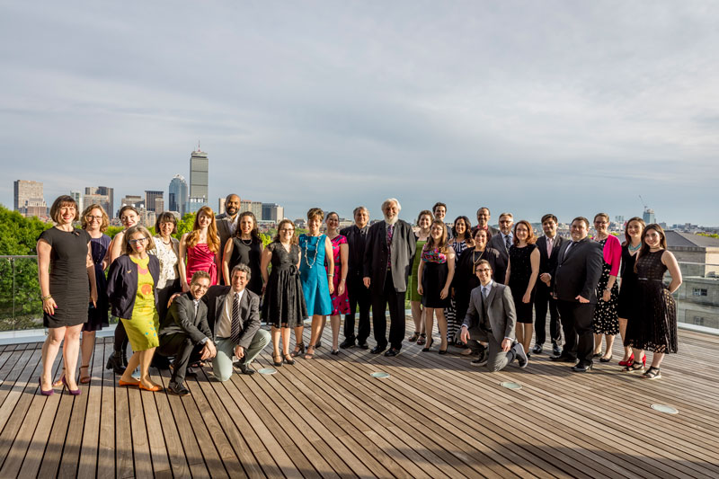 The From the Top staff are gathered for a photo with the Boston Skyline in the background