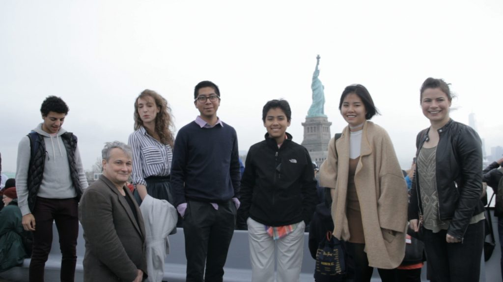 six young musicians and Christopher O'Riley with the statue of liberty in the background